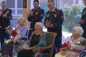 Soldiers from the 3rd Heavy Brigade Combat Team, 3rd Infantry Division, give a round of applause to Dorothy Grogan as she is named the first Ms. Magnolia Manor, Friday, at the Magnolia Manor assisted living community as part of Senior Citizens' Week. Sledgehammer soldiers escorted the contestants down the runway and during the evening attire portion of the pageant.
